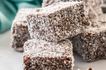 A pile of lamingtons with one broken in half and a turquoise napkin in the background