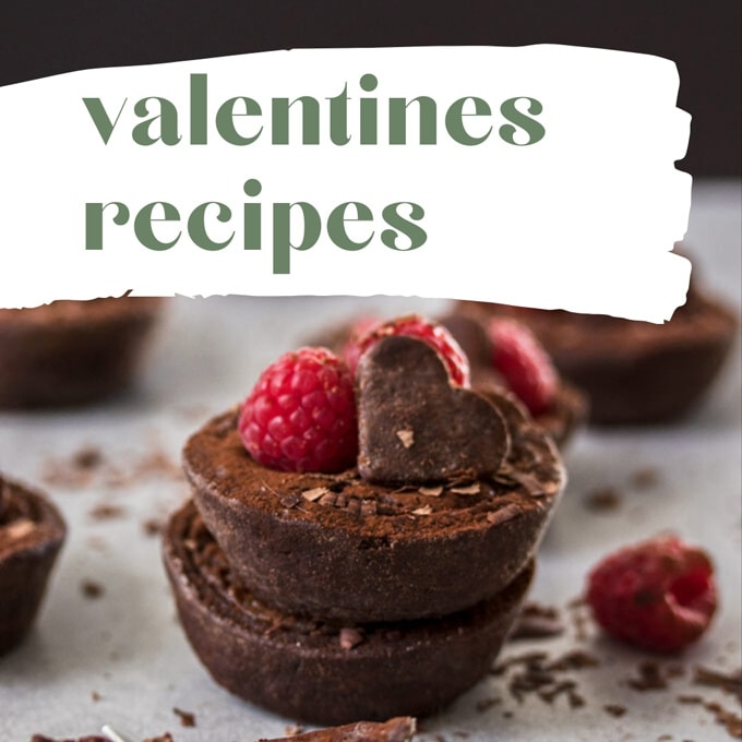 Two small chocolate tarts topped with raspberries and a chocolate heart cookie