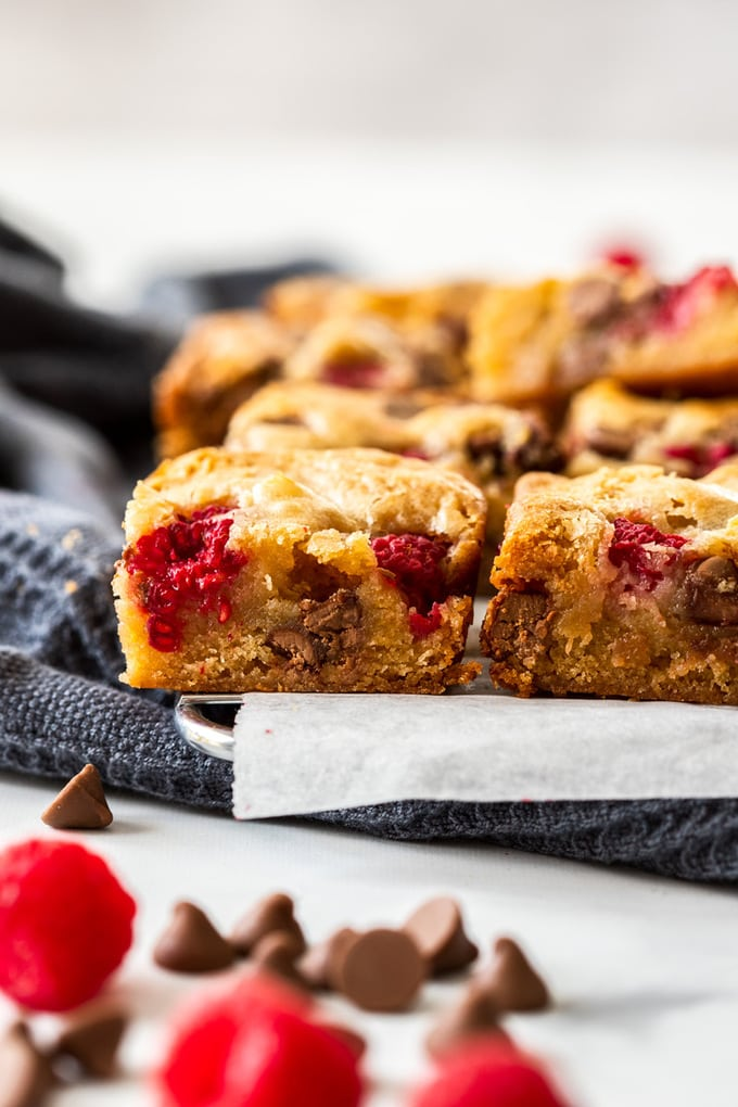 Close up of the side of some blondies with raspberries and chocolate chips nearby