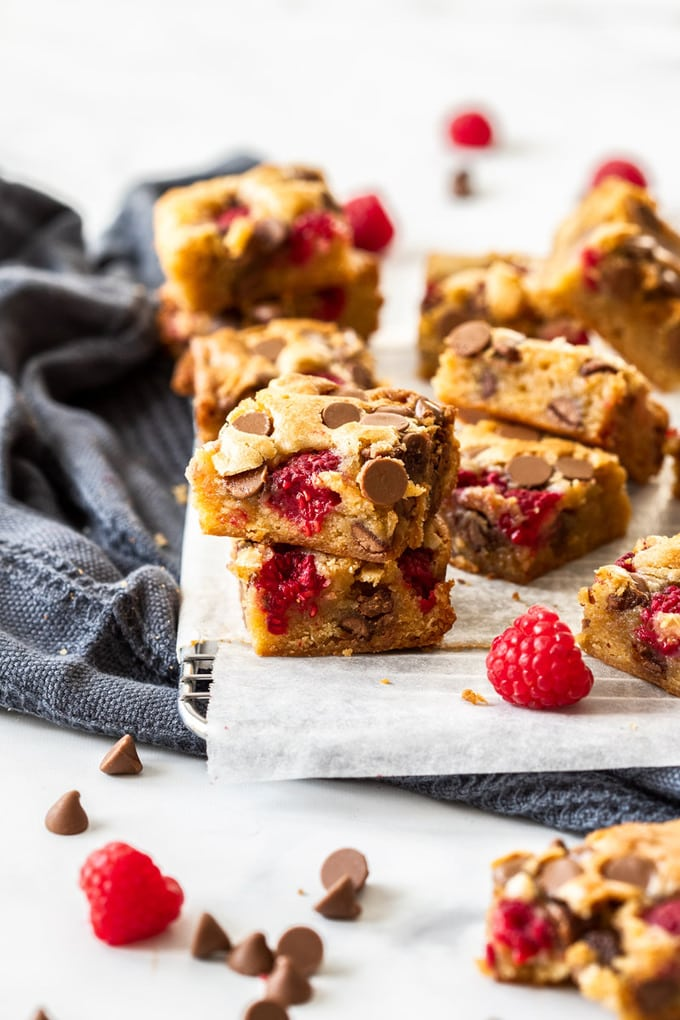 A batch of blondies with chocolate chips and raspberries on a wire rack with a grey tea towel nearby