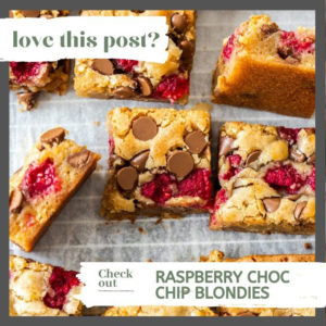 A batch of blondies with chocolate chips and raspberries on a wire rack