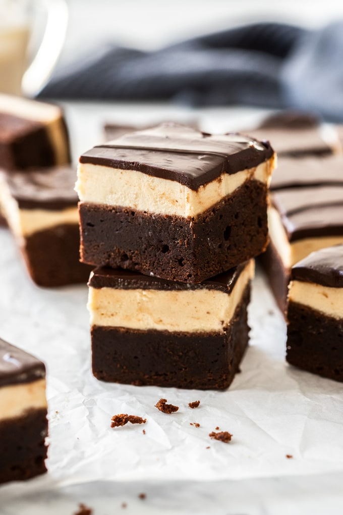 A stack of two baileys brownies on a sheet of baking paper with more brownies around them.