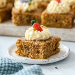 A closeup of a carrot cake bar on a small white plate. A tray of more in the background