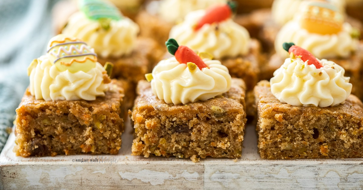 Closeup of 3 carrot cake bars on a white wooden board