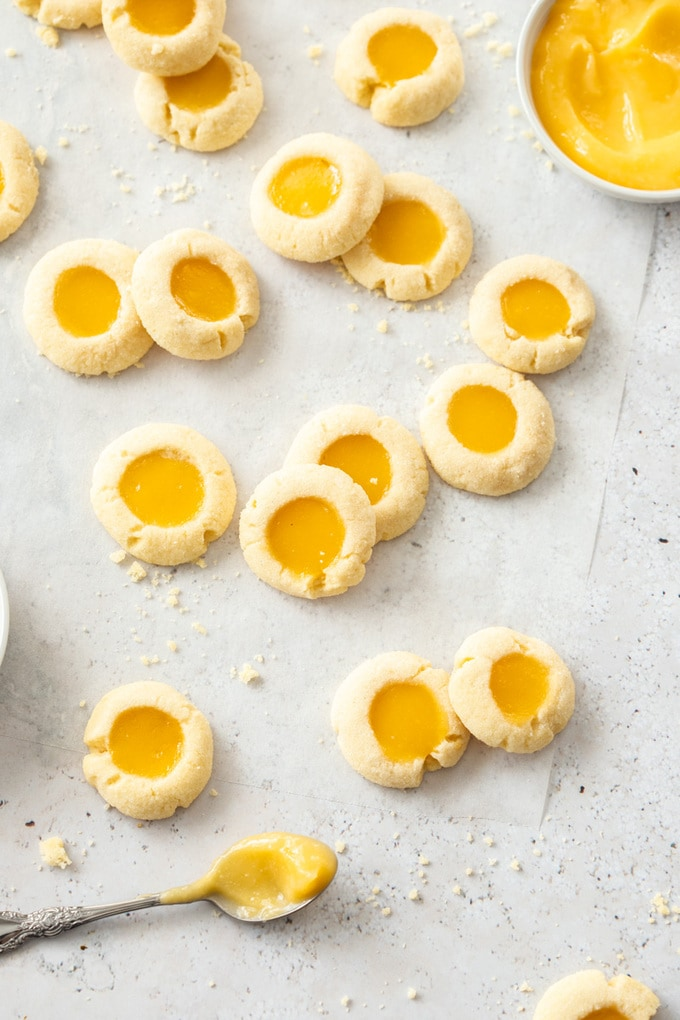 A batch of lemon curd cookies on a sheet of baking paper with a spoon of lemon curd next to them