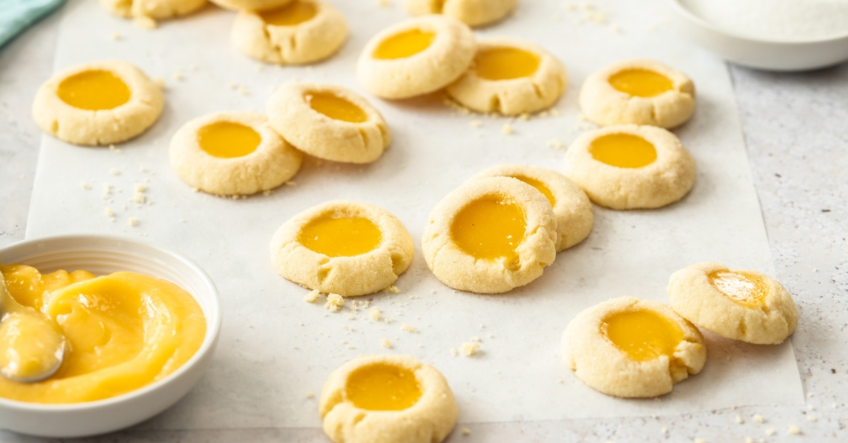 A batch of lemon curd cookies on a sheet of baking paper with a dish of lemon curd next to them