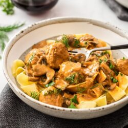 A grey bowl filled with meatball stroganoff with a glass of wine in the background
