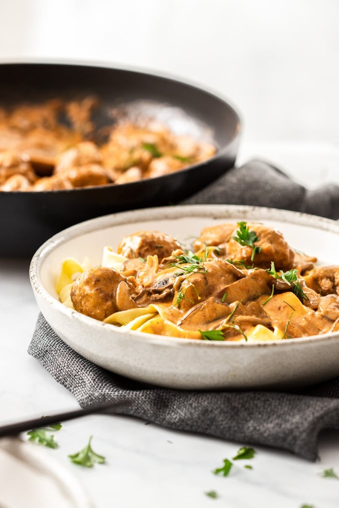 A grey bowl filled with meatball stroganoff with a black pan in the background