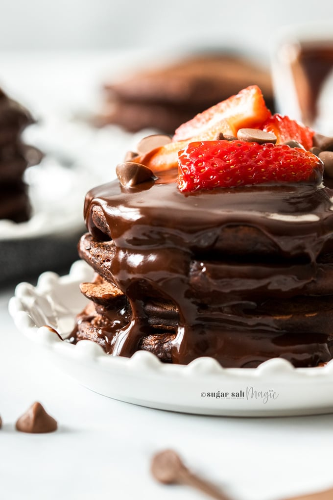 Close up of a stack of chocolate pancakes on a white plate, topped with strawberries chocolate chips and chocolate syrup