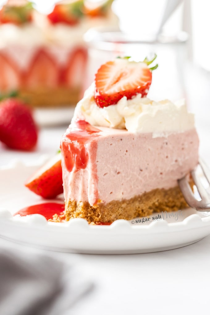 A slice of strawberry cheesecake with a bite taken out on a white plate
