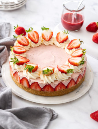 A pink cheesecake topped with strawberries on a marble background