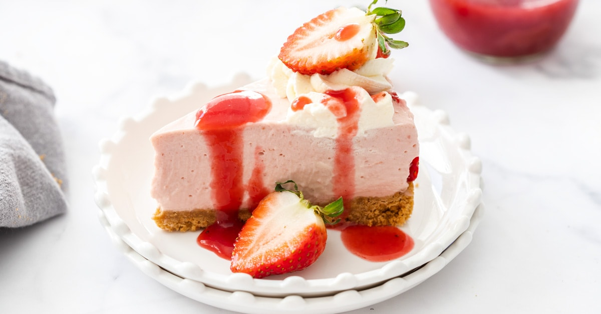 A slice of strawberry cheesecake on a white plate
