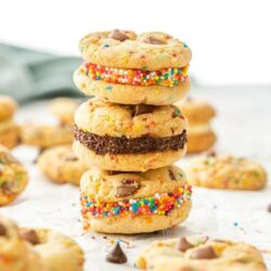 A stack of funfetti cookies surrounded by more and a small bowl of sprinkles