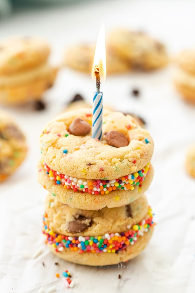A stack of funfetti cookies surrounded by more with a candle sticking out the top