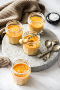 Small glass jars on a grey platter, filled with caramel custard. One has a spoon sitting on top