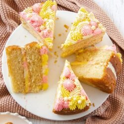 5 slices of vanilla cake on a white cake plate with a pink crocheted dish towel beneath