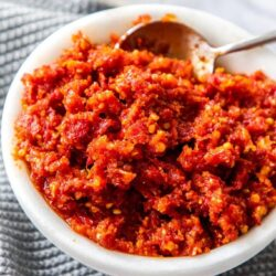 A white bowl of tomato pesto which sits on a grey crocheted napkin