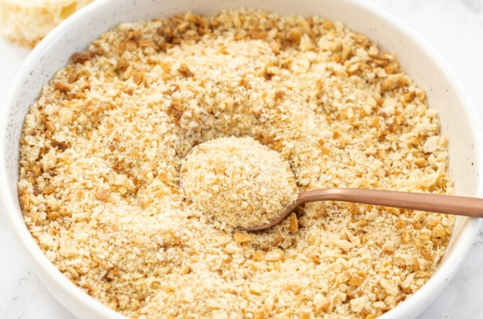 A white bowl filled with breadcrumbs with a spoon in it