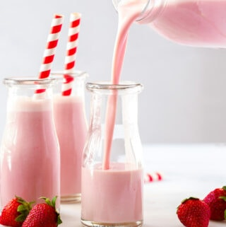 Two bottles of strawberry milk, with more being poured into a third bottle