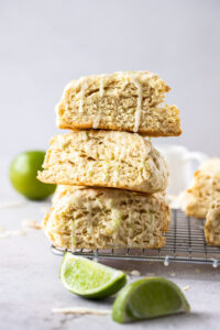 3 scones stacked on a wire rack. Lime wedges in front. whole lime in background. Grey bench top
