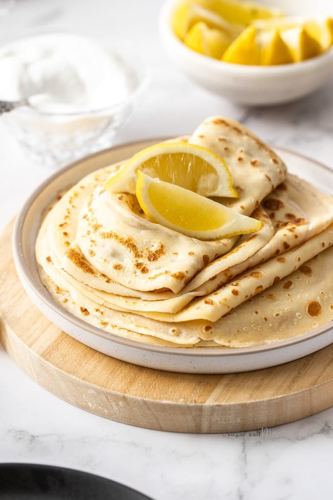 A white plate topped with a stack of english pancakes and wedges of lemon
