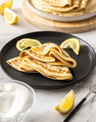 English pancakes folded and stacked on a black plate with lemon wedges nearby