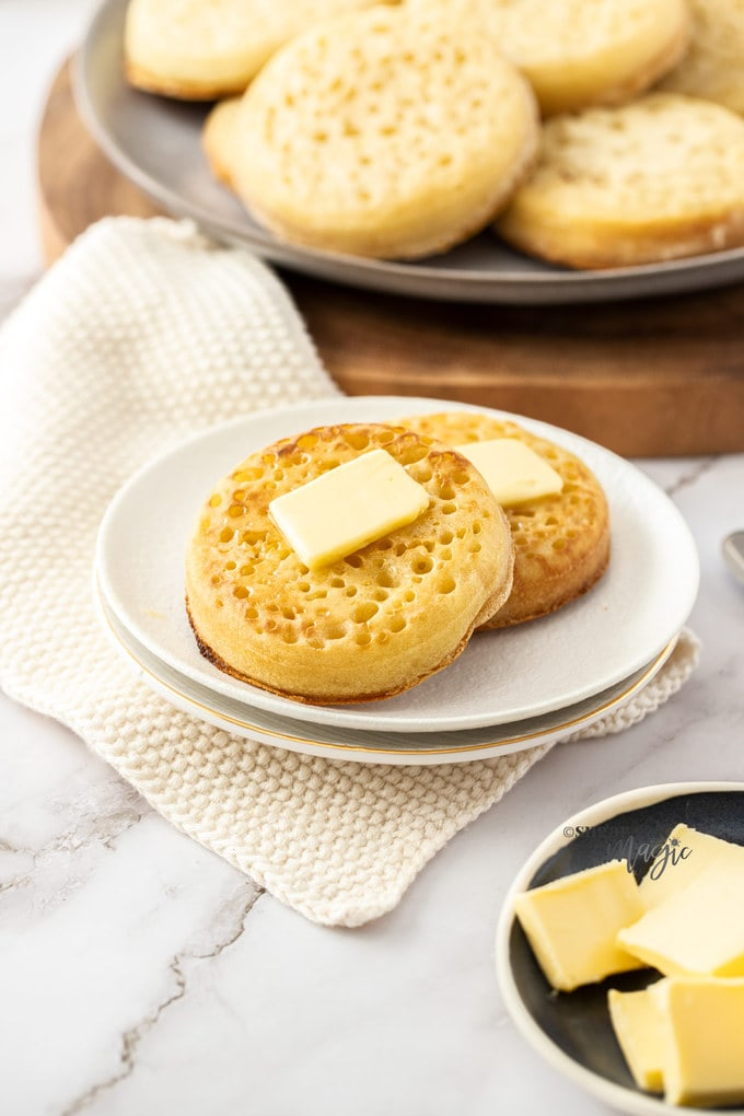 Two crumpets on a white plate with butter on top.