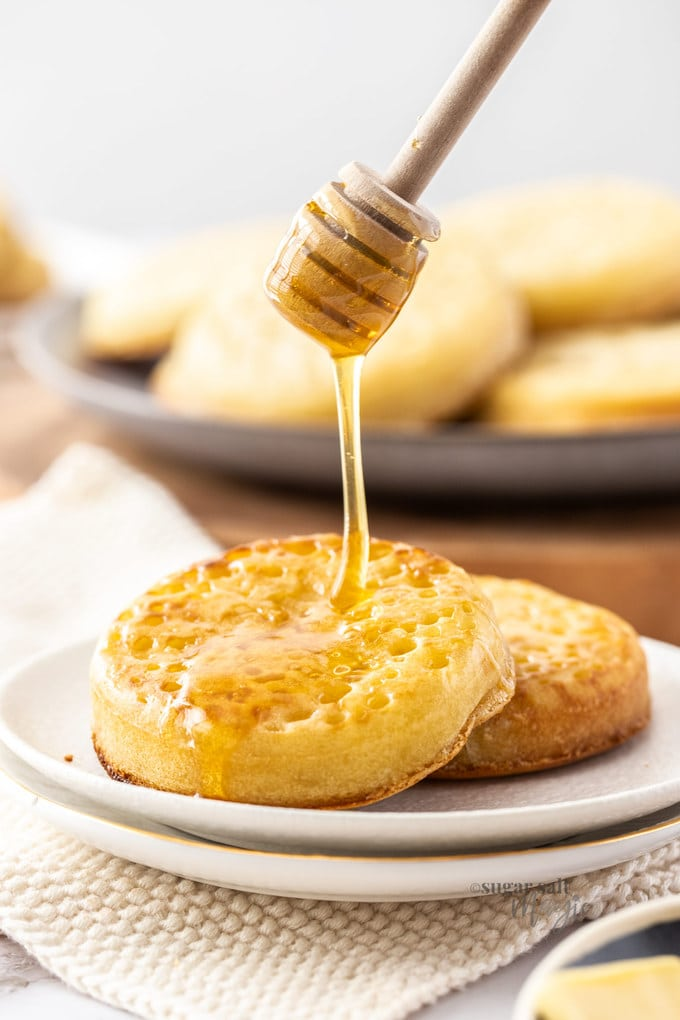 Two crumpets on a white plate with honey being drizzled over