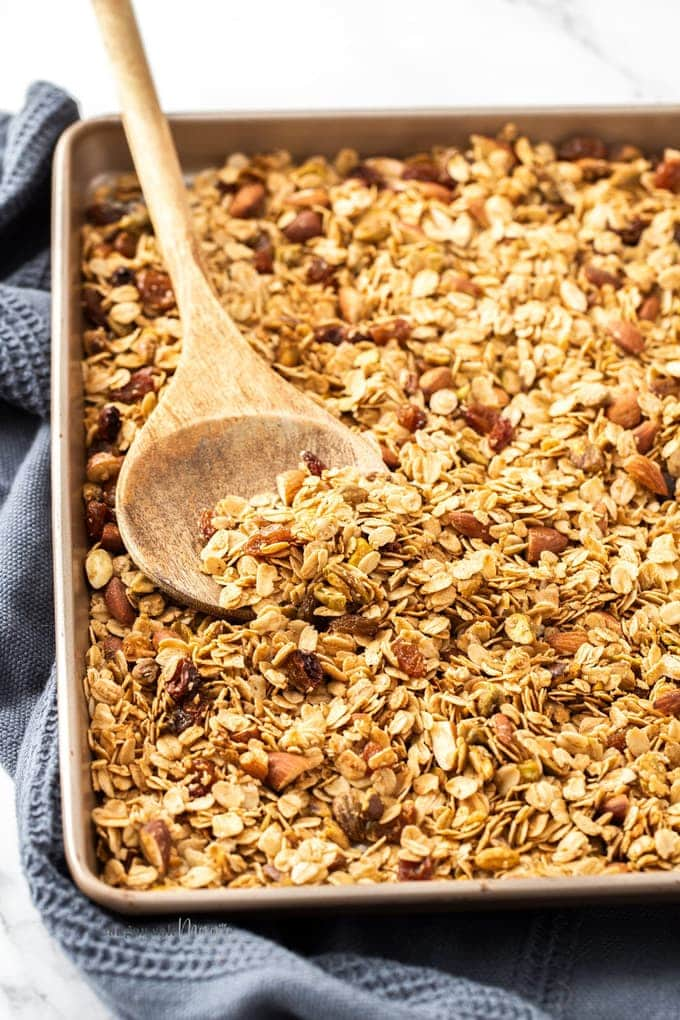 A batch of granola on a rose gold baking tray with a grey tea towel underneath