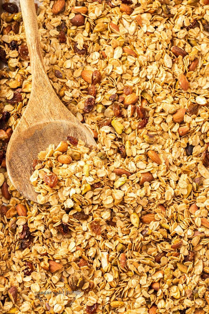 Closeup of a batch of granola with a wooden spoon in it