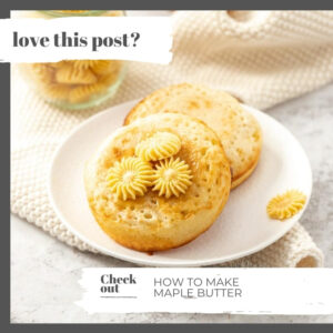 A white plate with two crumpets, topped with pats of butter