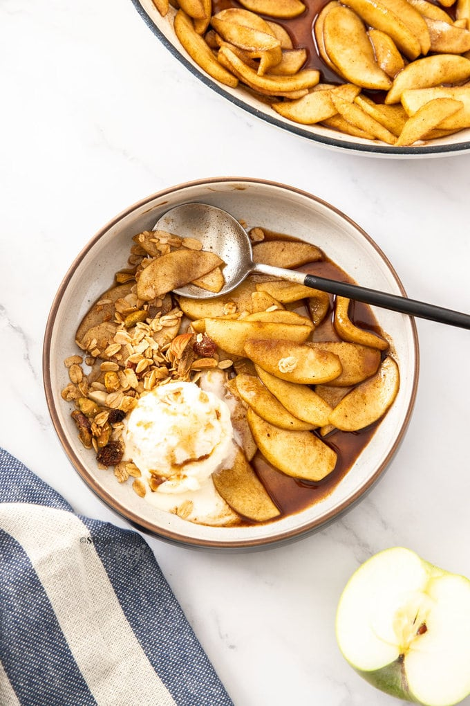 A bowl filled with cinnamon apples, ice cream and granola
