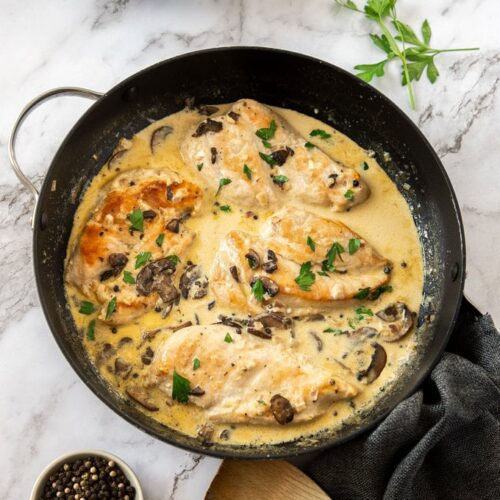 4 chicken breasts in a black skillet in a creamy sauce.