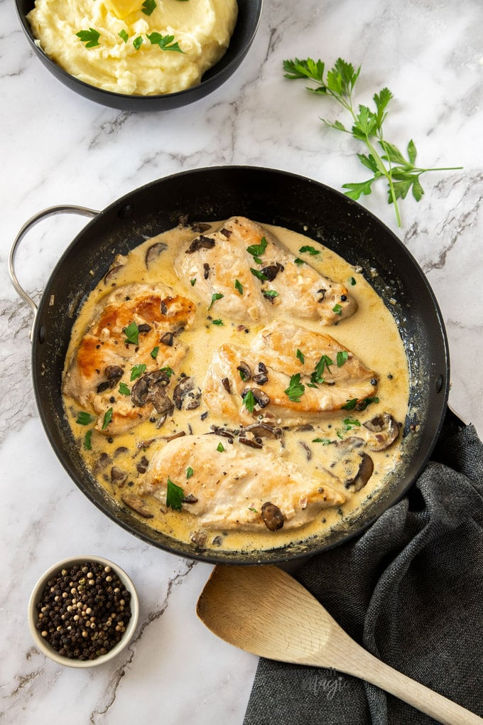 4 chicken breasts in a black skillet in a creamy sauce