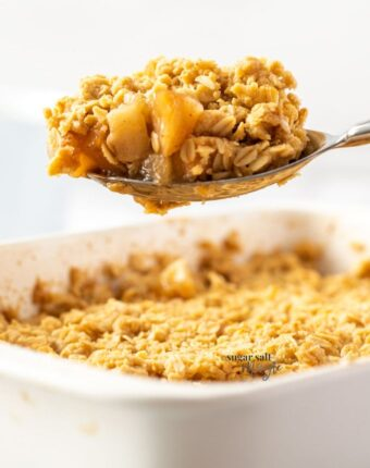 A spoon topped with apple crumble hovering above a dish full
