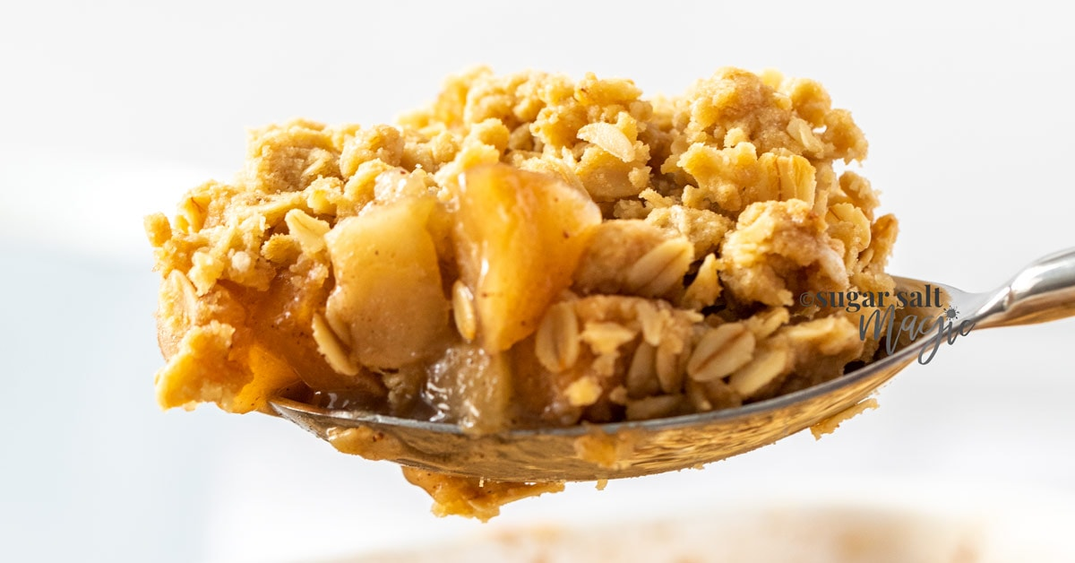 A spoon topped with apple crumble