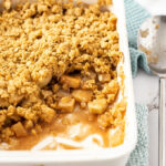 A white casserole dish filled with apple crumble