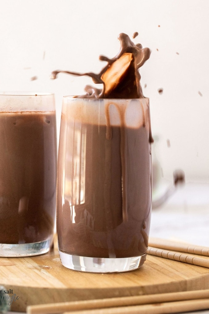 A glass of chocolate milk with a splash coming out the top
