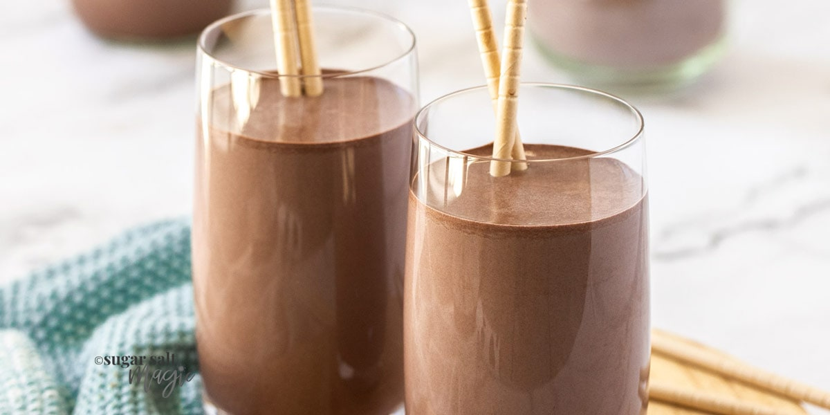 2 glasses of chocolate milk sitting on a small wooden platter