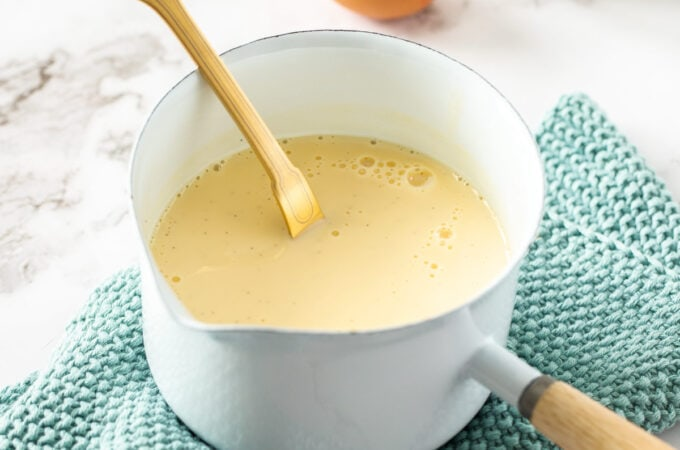 A small white saucepan filled with creme anglaise