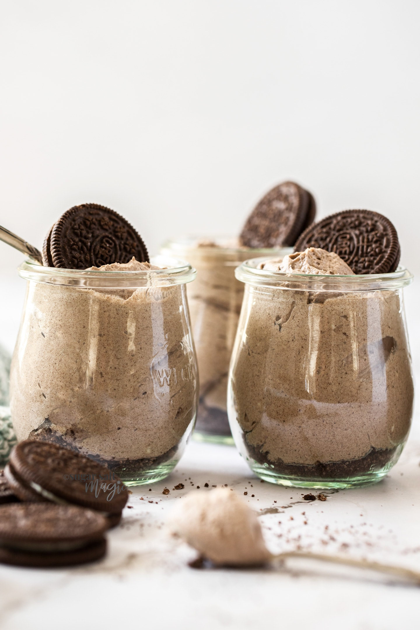 glass jars filled with oreo mousse with oreos on top