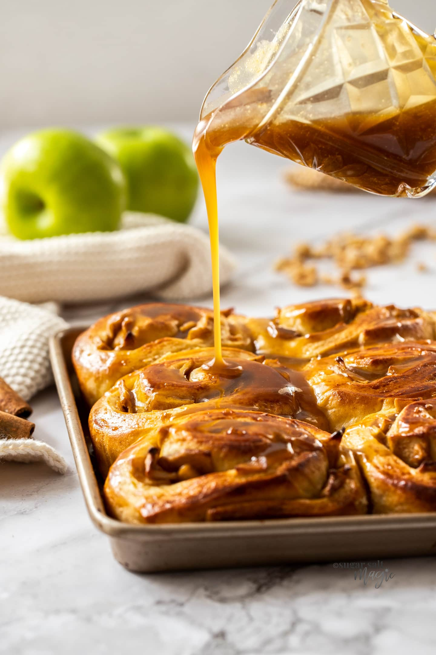 Caramel sauce being poured over cinnamon rolls