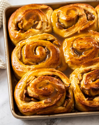 A gold baking tray filled with cinnamon rolls