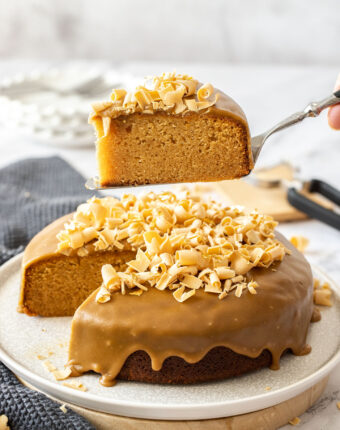 A slice of caramel cake being held above the remaining cake