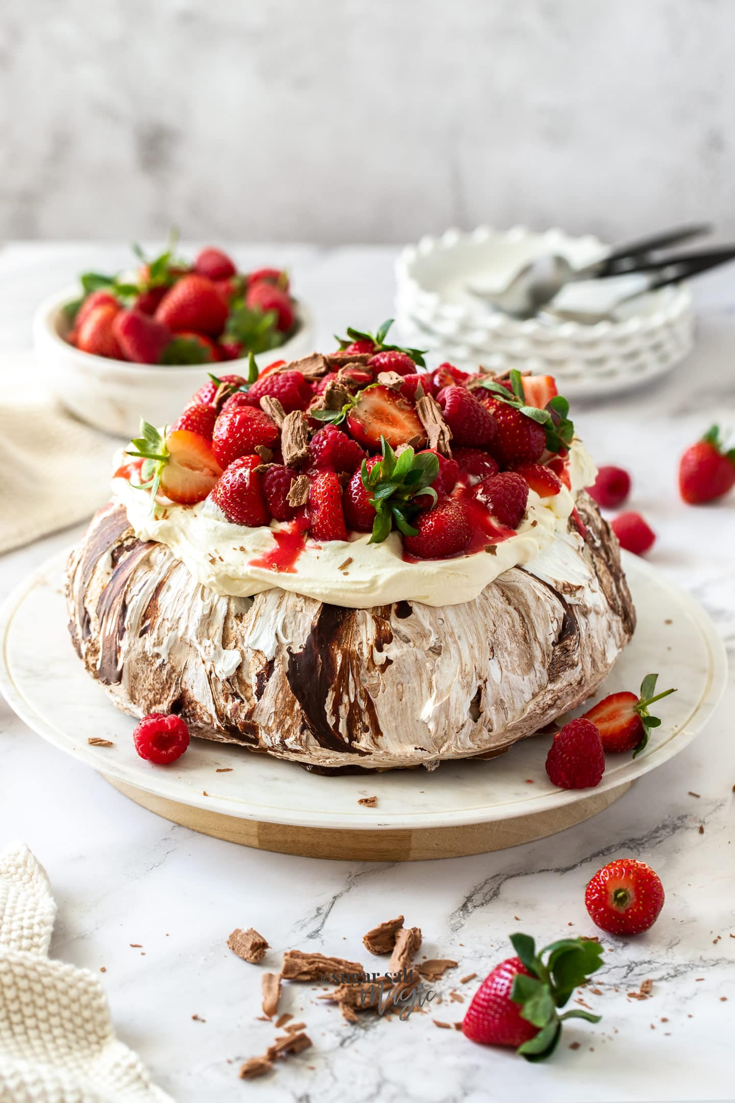A chocolate pavlova topped with cream and berries on a white cake plate