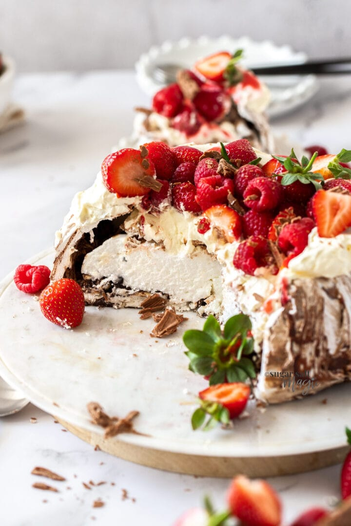 A chocolate pavlova topped with cream and berries that has been cut open.