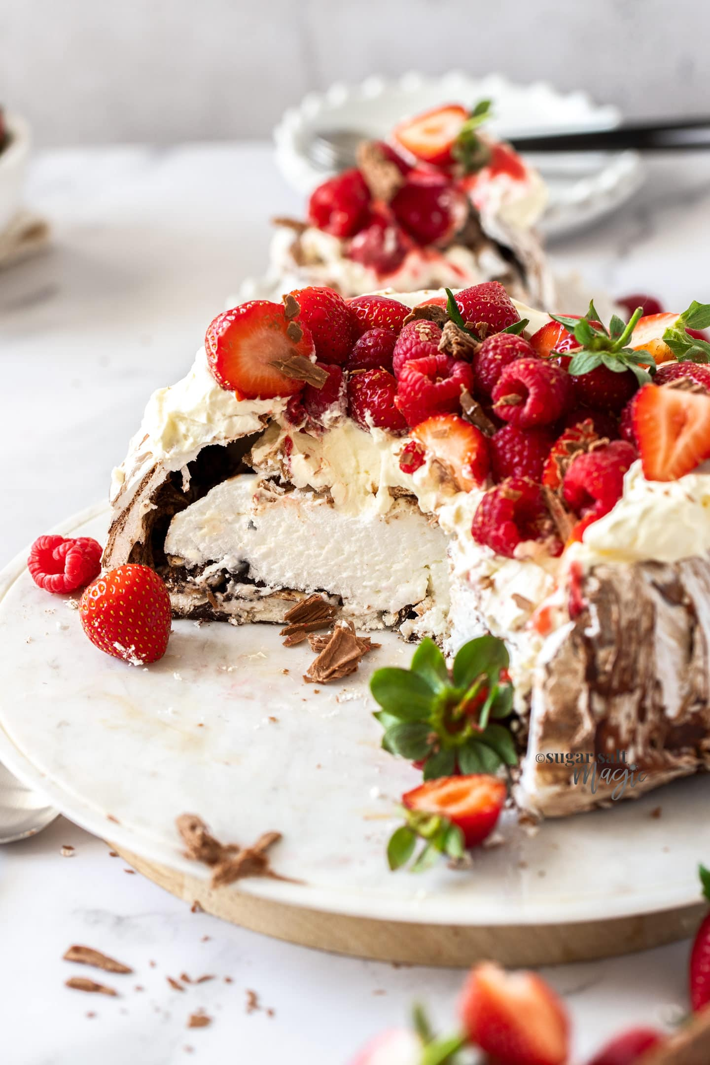 A chocolate pavlova topped with cream and berries that has been cut open