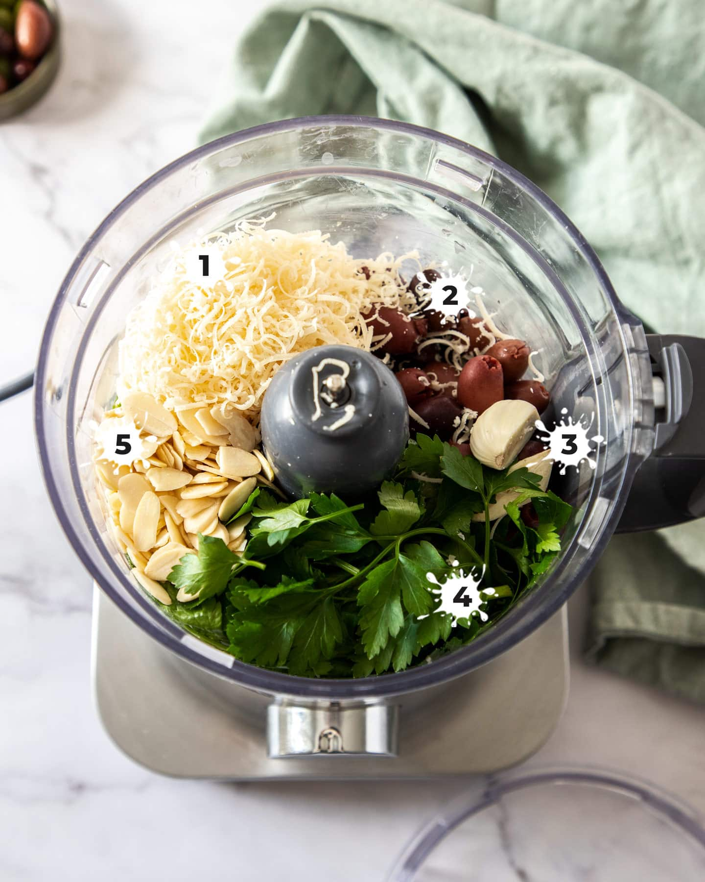 A food processor bowl filled with ingredients for olive pesto