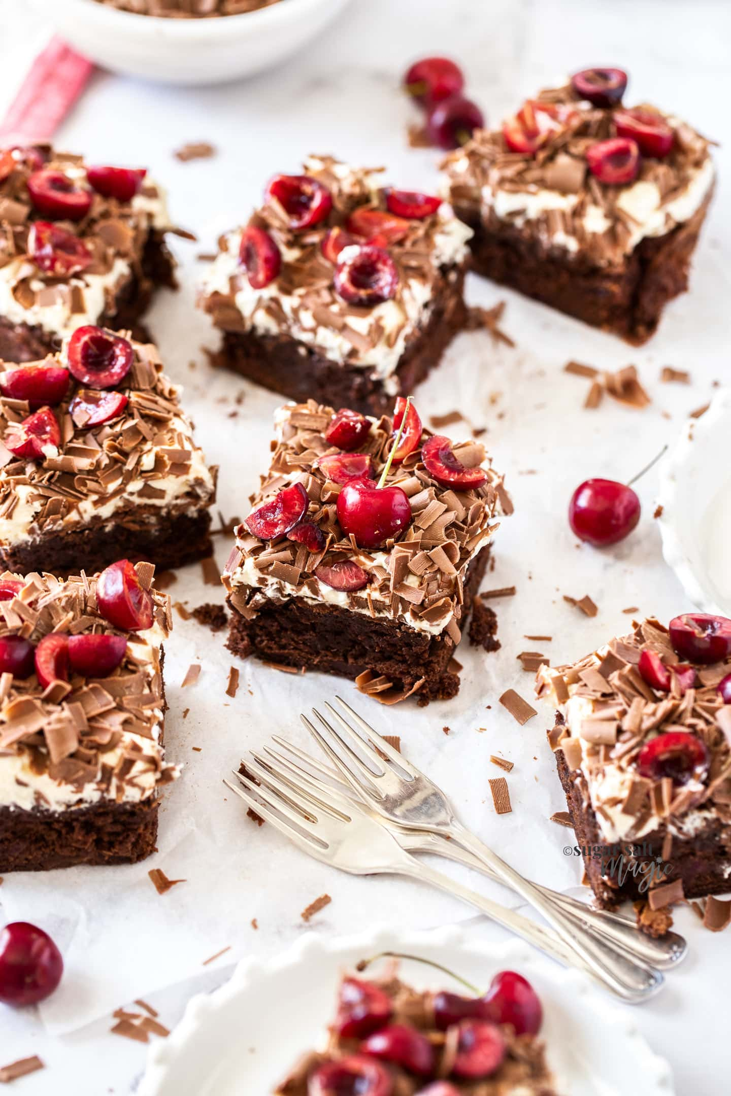A batch of brownies topped with cream, cherries and chocolate shavings