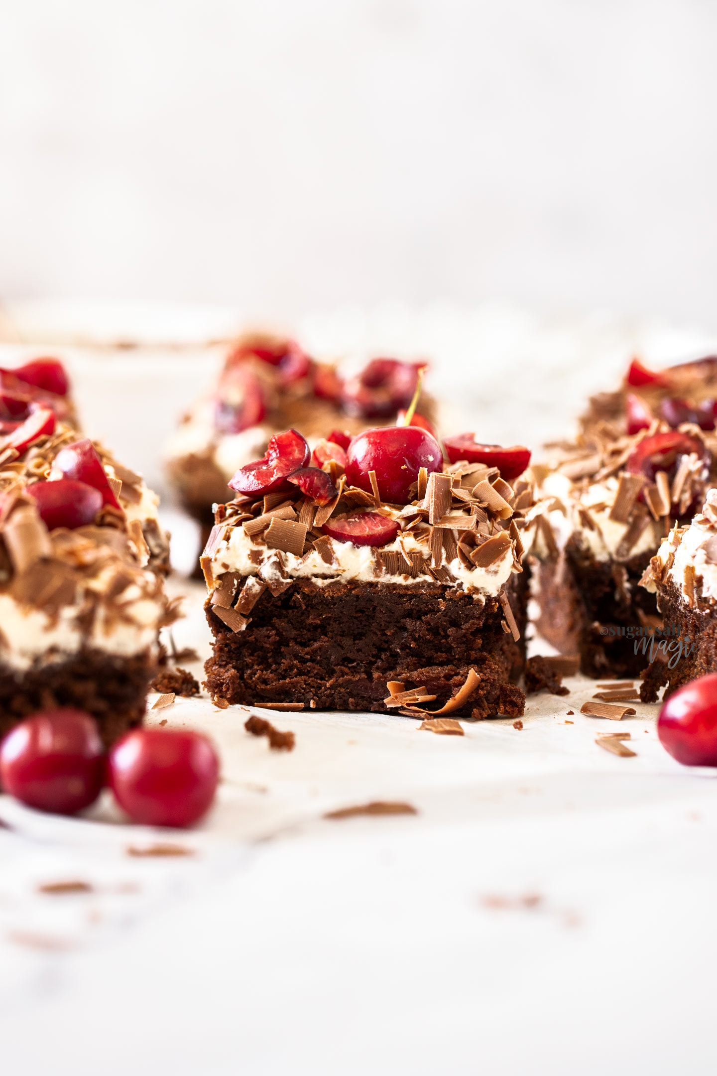 Closeup of a brownie topped with cream and cherries on a white surface